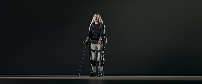 A woman is seen wearing an EKSO suit and holing crutches
